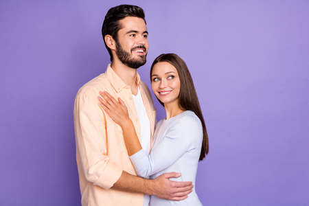 Photo of cheerful married couple look empty space hug harmony dream happy life isolated on purple color background