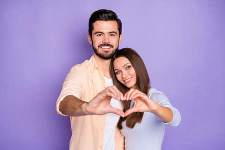 Photo of bristled brunette man charming woman make hands heart figure hug honeymoon isolated on violet color background