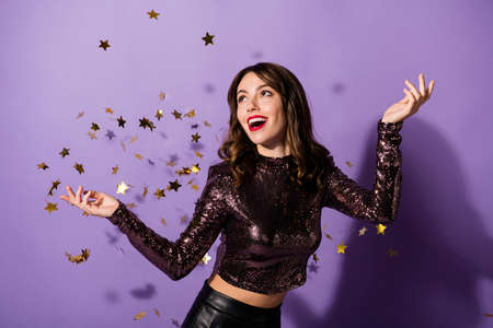 Portrait of gorgeous glamorous cheerful girl having fun sequins flying isolated over bright violet color background