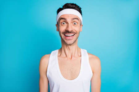 Portrait of impressed sporty man open mouth scream wear white singlet tank-top isolated over blue color background Standard-Bild