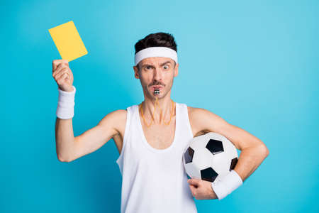 Photo of serious brown haired guy hold show yellow card football judge whistle isolated on blue color background