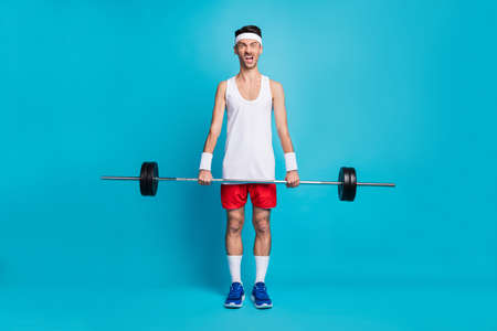 Full length portrait of focused sportive man hands hold barbell open mouth scream isolated on blue color background