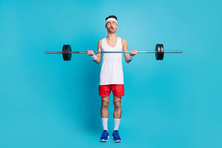 Photo of young sportsman lift heavy barbell grimacing exercise bodycare isolated over blue color background Standard-Bild