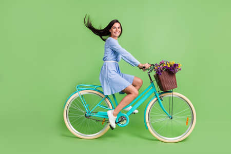 Photo of pretty funny young lady wear dotted clothes smiling driving bicycle isolated green color background Imagens