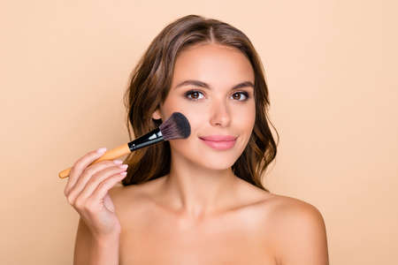 Photo of young happy beautiful girl applying highlighter blush on cheeks with makeup brush isolated on beige color background Фото со стока