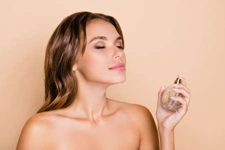 Photo of young beautiful charming dreamy woman wear no clothes apply perfume isolated on beige color background Standard-Bild