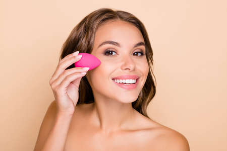 Photo of young beautiful smiling woman applying foundation on cheek with beauty blender isolated on beige color background