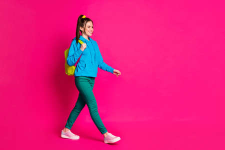 Full length photo of sweet young lady wear blue sweater rucksack walking looking empty space isolated bright pink color background