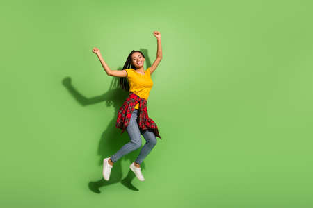 Full length photo of funny sweet dark skin woman wear yellow t-shirt jumping rising fists isolated green color background
