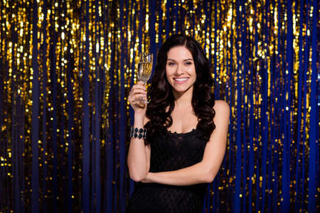 Portrait of stunning positive girl arm hold champagne glass look camera isolated on shiny decorated background