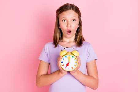 Photo of shocked amazed little teenage girl hold hands alarm clock time isolated on pink color background