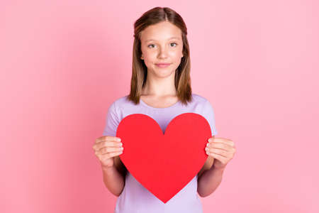 Photo of charming lovely sweet small girl hold hands red paper heart isolated on pink color background