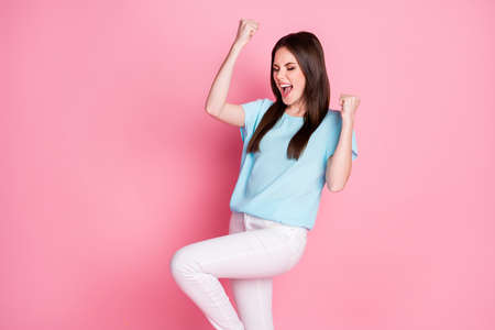 Photo of ecstatic lucky girl win lottery raise fists scream yeah wear good look outfit isolated over pastel color background