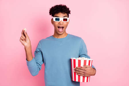 Photo of young black man amazed shocked surprised eat popcorn watch film 3d glasses isolated over pastel color background