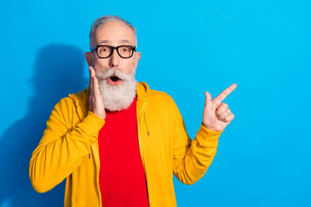 Photo of shocked surprised amazed mature man point finger copyspace advertise product isolated on blue color background