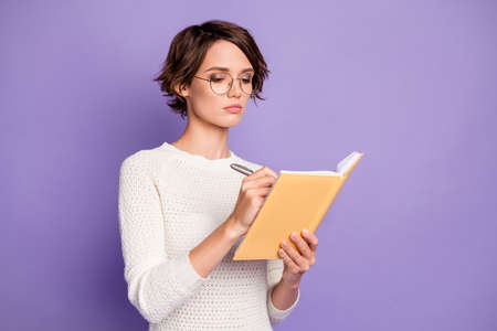 Photo portrait of concentrated clever student writing essay in copybook isolated on pastel purple color background