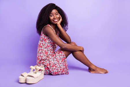 Full length body size photo model sitting barefoot wearing summer floral dress isolated pastel violet color background