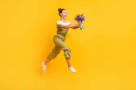 Full length body size view of beautiful trendy cheerful girl jumping going carrying fresh flowers isolated over bright yellow color background