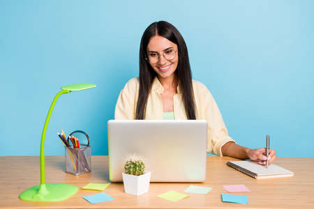 Photo of cheerful happy young brunette lady look laptop sit desk work wtite note isolated on pastel blue color background