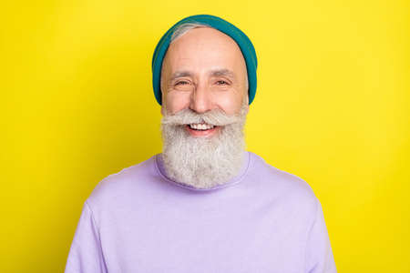 Photo of funky cool mature man dressed purple pullover headwear smiling isolated yellow color background