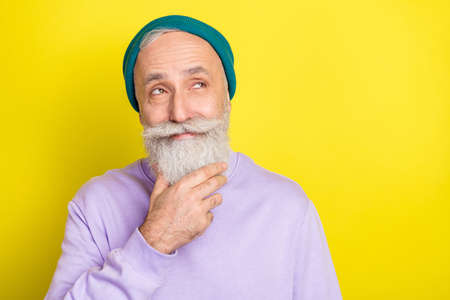 Photo of tricky thoughtful mature man dressed purple pullover arm chin smiling looking empty space isolated yellow color background