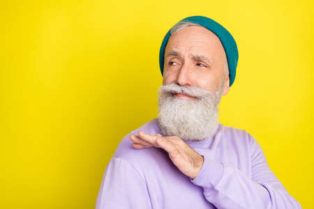 Photo of thoughtful sweet mature man dressed purple pullover headwear arm shoulder looking empty space isolated yellow color background