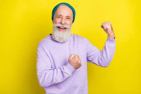 Photo of sweet lucky mature man dressed purple pullover headwear smiling rising fists isolated yellow color background Stok Fotoğraf
