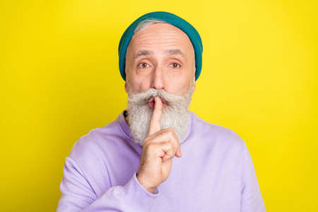 Photo of strict cute mature man dressed purple pullover headwear arm lips ask shut up isolated yellow color background Stok Fotoğraf