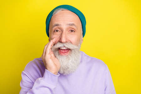 Photo of funny handsome age gentleman wear violet sweater headwear arm lips telling secret isolated yellow color background