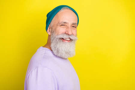 Photo of funky funny mature man dressed purple pullover headwear smiling empty space isolated yellow color background Stok Fotoğraf