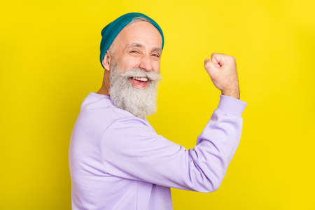 Photo of pretty lucky age gentleman wear violet sweater headwear rising fist smiling isolated yellow color background Stok Fotoğraf