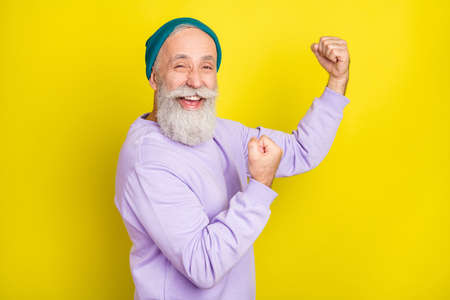 Photo of funny sweet mature man dressed purple pullover headwear smiling rising fist isolated yellow color background Stok Fotoğraf