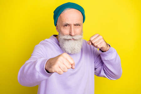 Photo portrait of senior man fighting wearing violet sweatshirt isolated on bright yellow color background Stok Fotoğraf