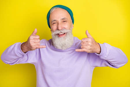 Photo portrait of senior man showing heavy metal sign smiling isolated on bright yellow color background