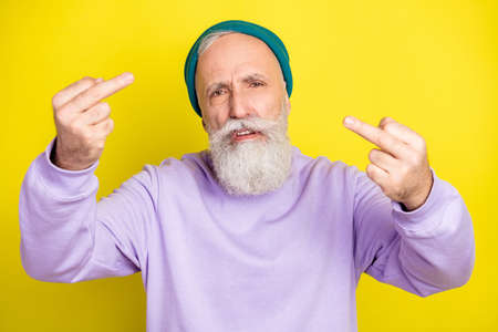 Photo portrait of senior man showing offensive fucking sign isolated on bright yellow color background