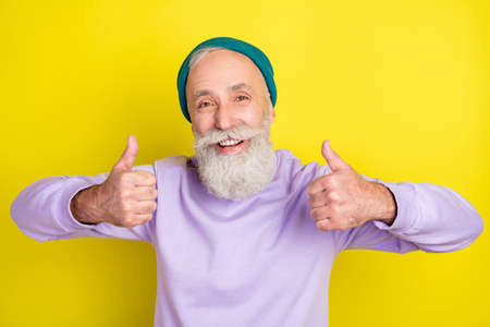 Photo portrait of senior man showing like thumb-up sign isolated on vivid yellow color background