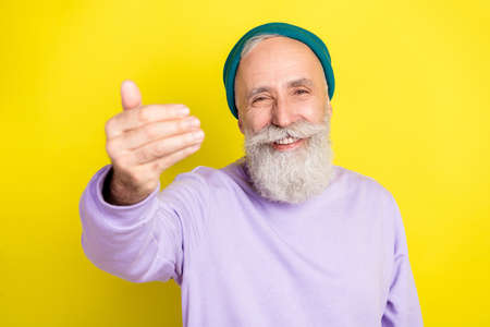 Photo portrait of elder man showing come on gesture inviting sign isolated on vibrant yellow color background