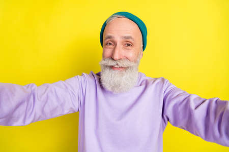 Photo portrait of elder cheerful man taking selfie smiling isolated on bright yellow color background