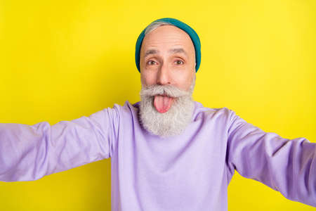 Photo portrait of elder man showing tongue taking selfie smiling isolated on bright yellow color background