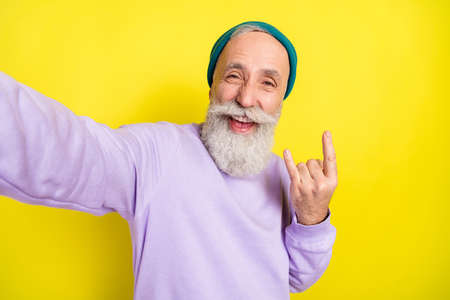 Photo portrait of elder man showing heavy metal sign smiling isolated on bright yellow color background