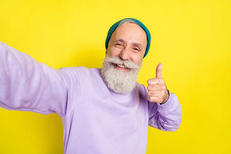 Photo portrait of elder man showing like thumb-up gesture smiling isolated on bright yellow color background Stok Fotoğraf