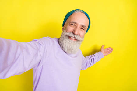 Photo portrait of elder man showing blank space taking selfie isolated on bright yellow color background