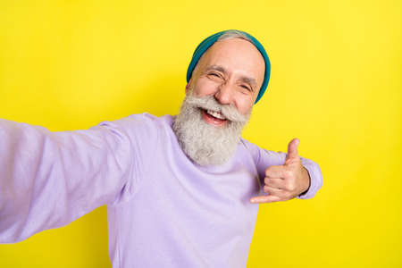 Photo portrait of elder man showing heavy metal gesture laughing isolated on vivid yellow color background