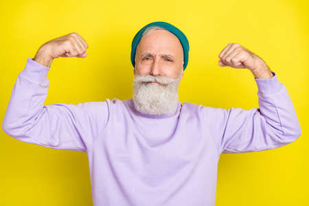 Photo portrait of elder man demonstrating strong muscles isolated on vibrant yellow color background