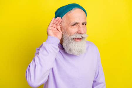 Photo portrait of elder man hearing news wearing sport outfit misunderstanding isolated on vibrant yellow color background