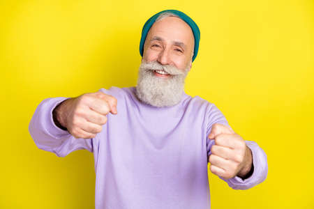 Photo portrait of elder man preparing to driving test imagine steering wheel isolated on vibrant yellow color background