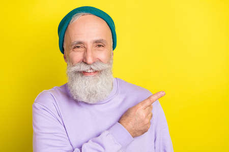 Photo portrait of elder man pointing copyspace smiling isolated on vibrant yellow color background