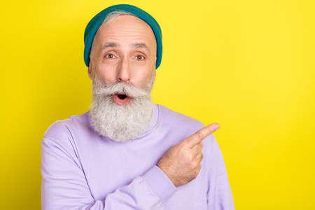 Photo portrait of amazed senior man pointing blank space amazed surprised isolated vibrant yellow color background