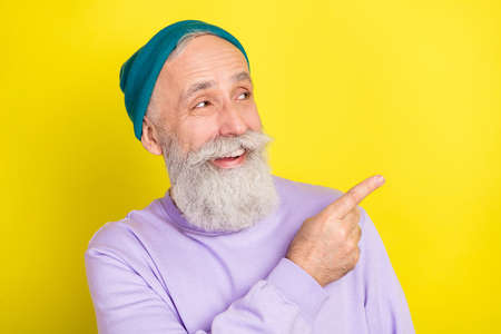 Photo portrait of amazed senior man pointing empty space smiling cheerful isolated bright yellow color background