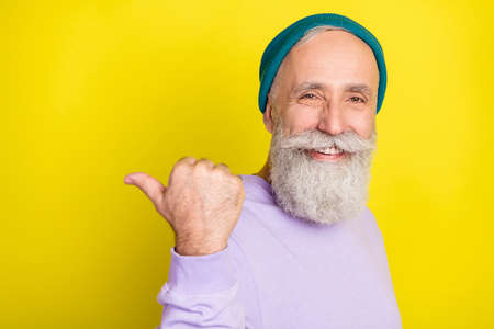 Photo portrait of senior man pointing thumb copyspace advising choosing isolated bright yellow color background
